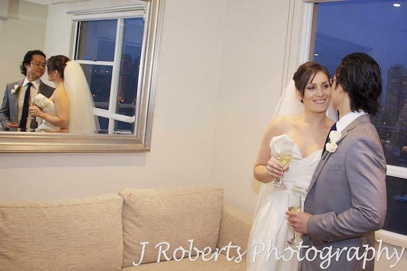 Bride and groom looking at each other with reflection in the mirror - wedding photography sydney
