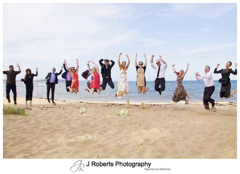 Couple and friends jumping on Long Reef Beach - wedding photography sydney