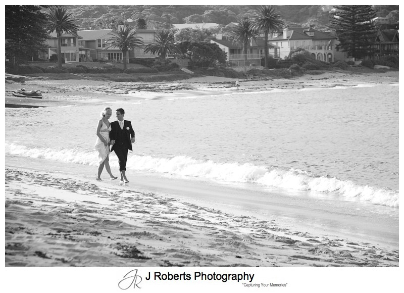 B&W of couple walking along Long Reef Beach - wedding photography sydney