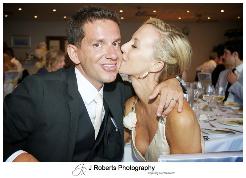 Bride kissing grooms cheek at wedding reception - wedding photography sydney