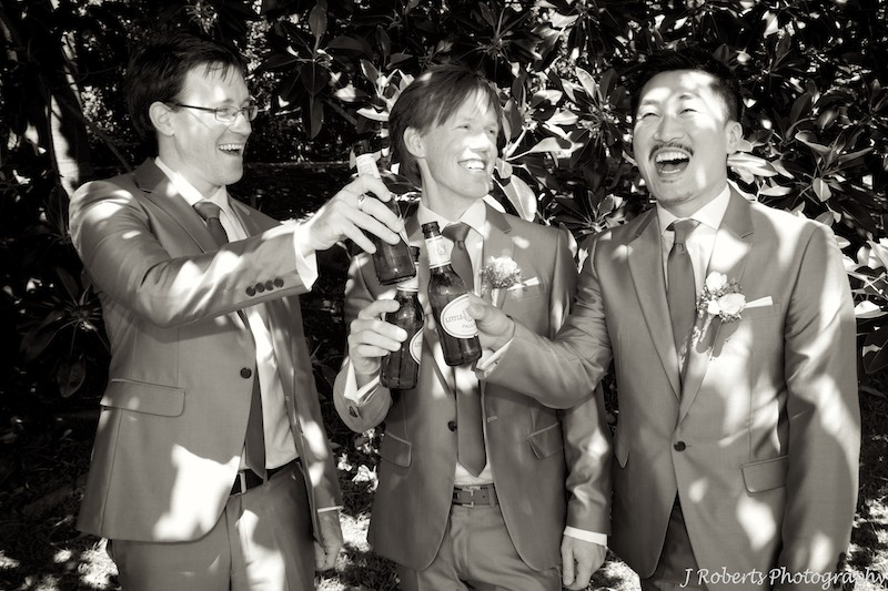 Groom and groomsmen celebrating - wedding photography
