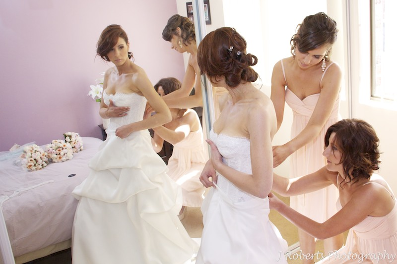 Bride being helped into her dress by bridesmaids - wedding photography sydney