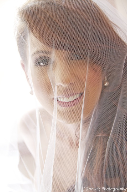 Bride looking up at the camera through her veil - wedding photography sydney