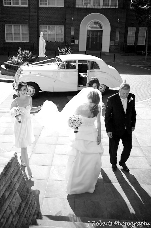 Bride arriving at the church being helped by bridesmaids - wedding photography sydney
