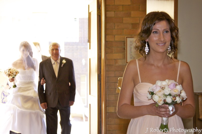 Bridesmaid walking down the aisle with bride and her father in the background - wedding photography sydney