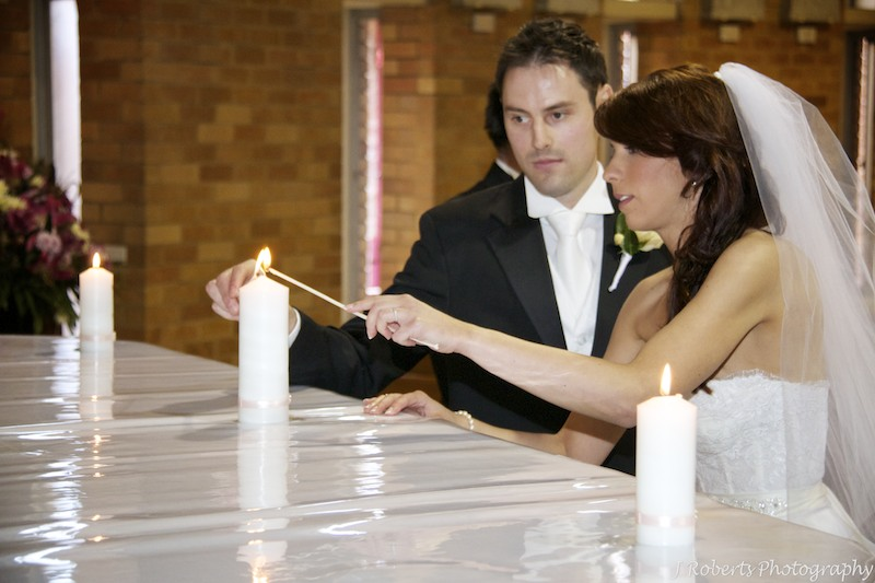 Lighting the marriage candle during the catholic wedding ceremony - wedding photography sydney