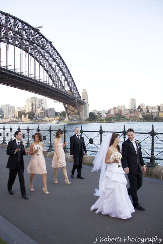 Bridal party walking beside the harbour with Sydney Harbour Bridge behind - wedding photography sydney