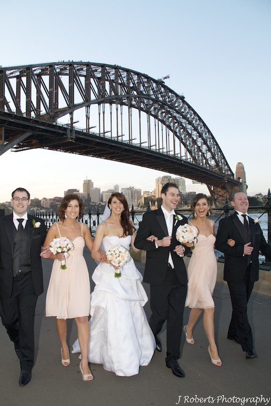 Bridal party walking arm in arm laughing - wedding photography sydney