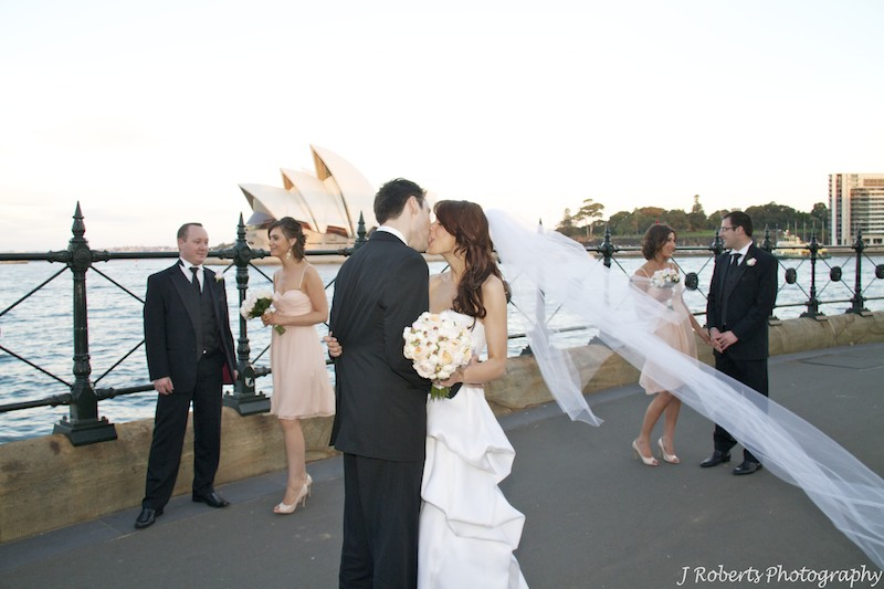 Couple Kissing with attendants around Sydney Opera House - wedding photography sydney