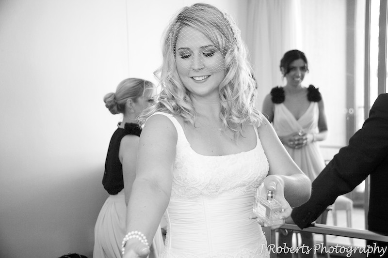 Bride spraying perfume as her final touch - wedding photography sydney
