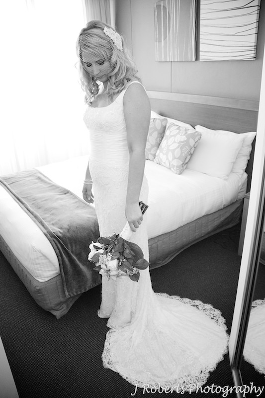 Bride looking down at her flowers in hotel room at Sebel Manly Beach - wedding photography sydney