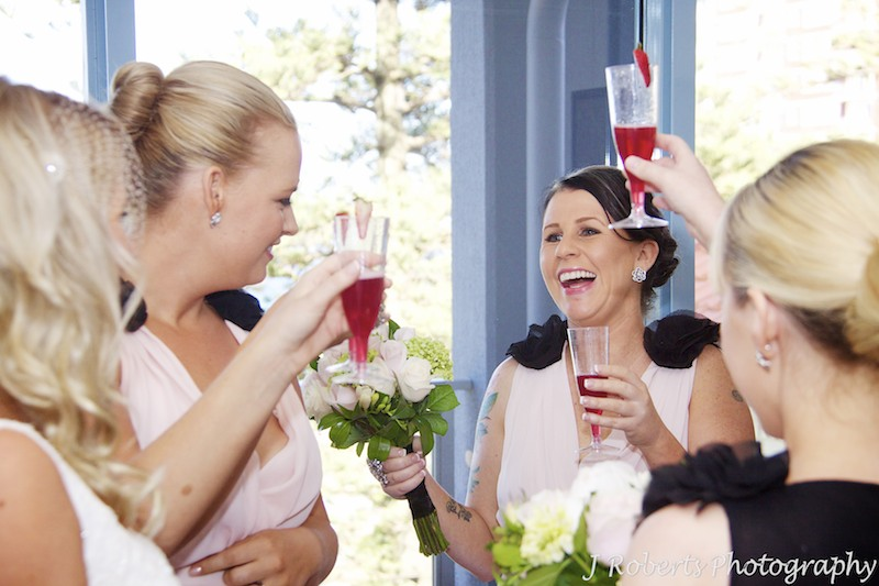 Bridesmaid cheers with champagne - wedding photography sydney