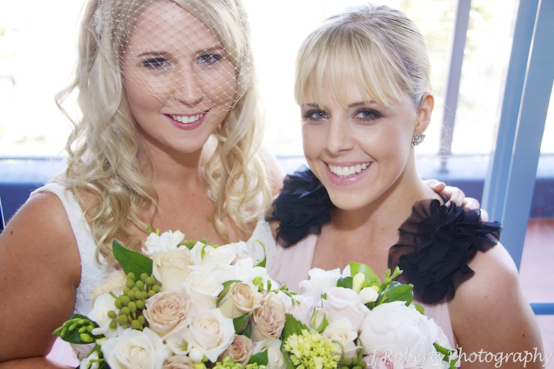 Bride and bridesmaid smiling up at camera - wedding photography sydney