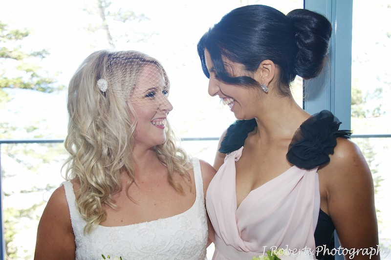 Bride laughing with bridesmaid - wedding photography sydney