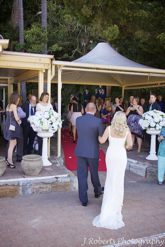 Bride walking into courtyard at Le Kiosk Shelley Beach for wedding ceremony - wedding photography sydney