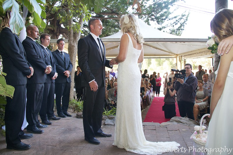 Bride and groom exchange rings in courtyard at Le Kiosk Shelley Beach - wedding photography sydney