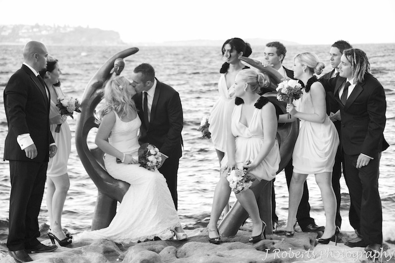 B&W of bridal couple kissing with bridal party looking on - wedding photography sydney