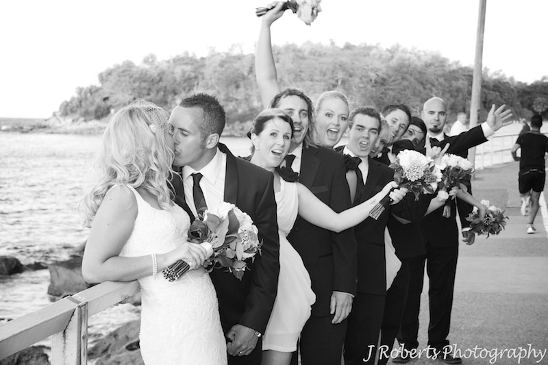 B&W bridal couple kissing and bridal party cheering - wedding photography sydney