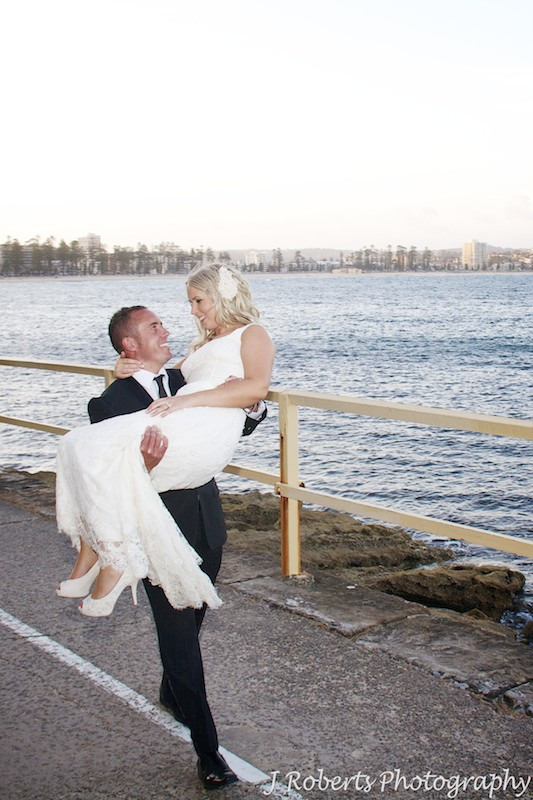 Groom carrying bride along waters edge - wedding photography sydney