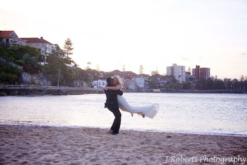 Groom swinging bride in the air on Shelley Beach - wedding photography sydney