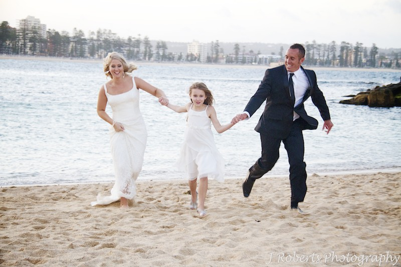 Bride and groom running up the beach with their daughter - wedding photography sydney