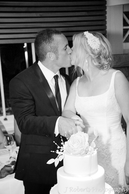 Bride and groom kissing after cutting the wedding cake - wedding photography sydney