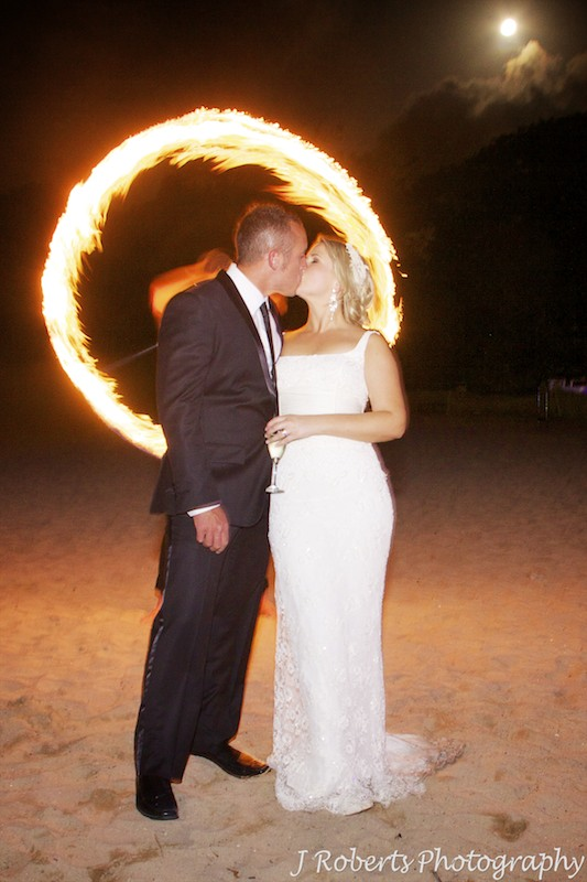Bride and groom kissing in front of fire dancing ring of fire and full moon - wedding photography sydney