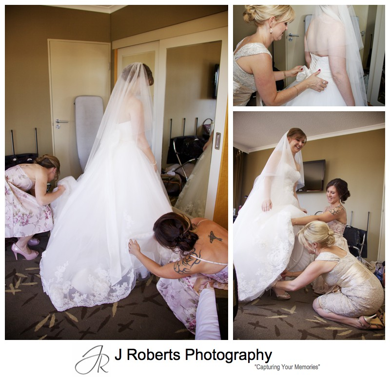 Bride getting into her dress with help from attendants - wedding photography sydney