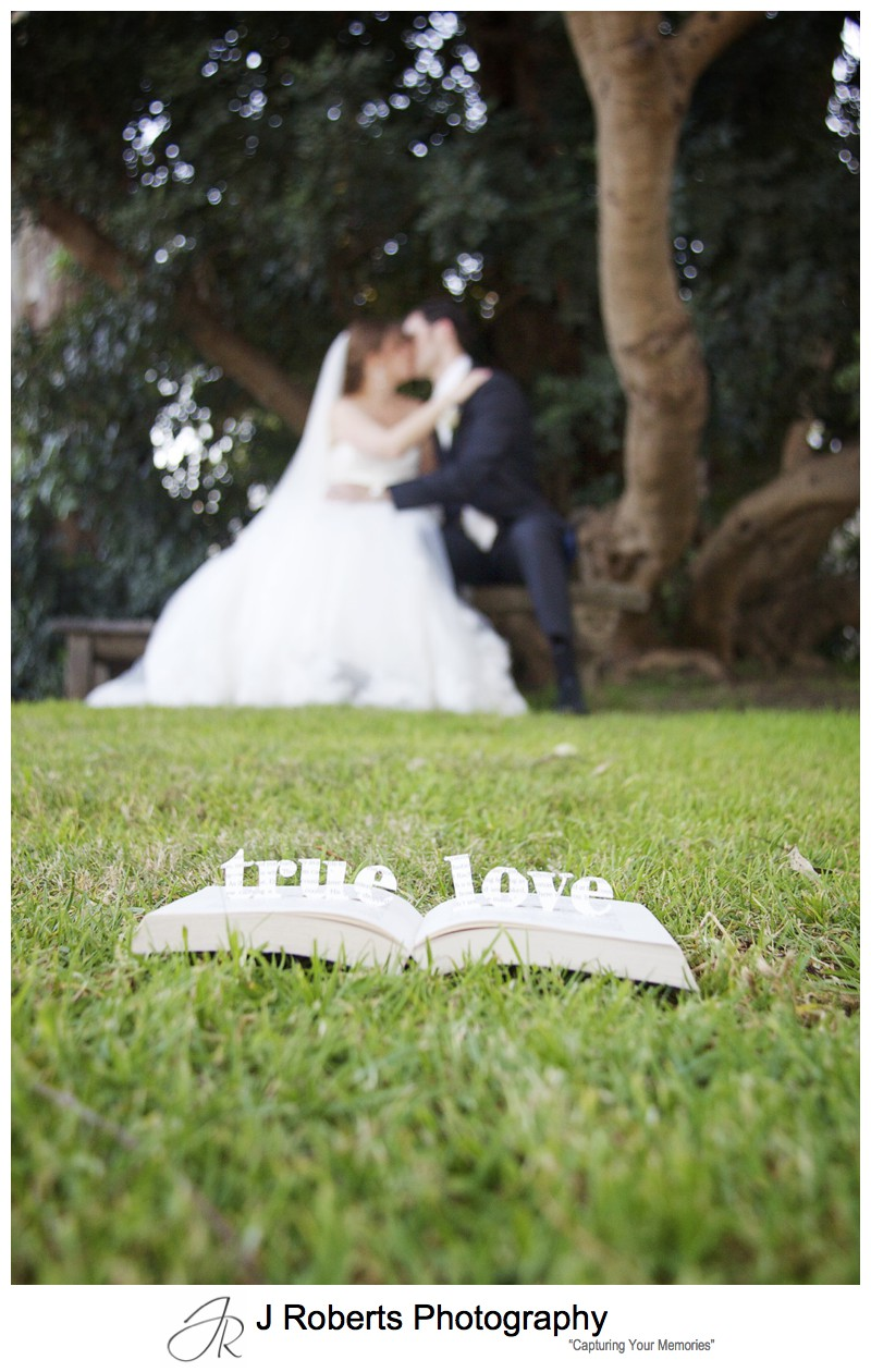 Bride and groom with 'true love' carved in a book - wedding photography sydney