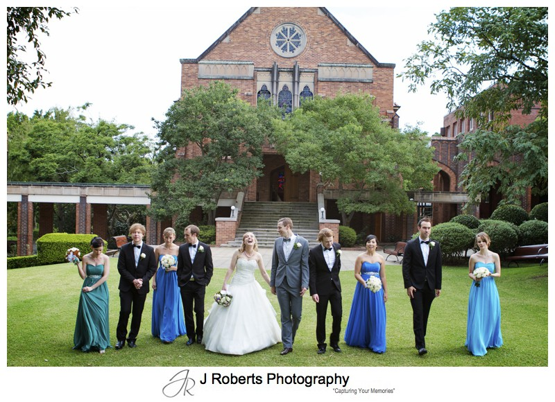 Bridal party walking on the lawns at the front of Pymble Ladies College Chapel - wedding photography sydney