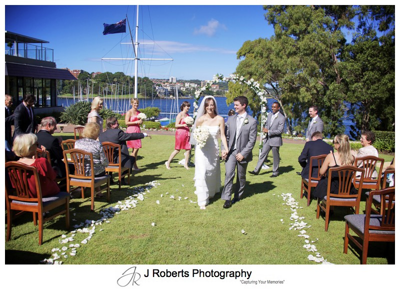 Bride and groom leaving as Mr & Mrs on the RSYS lawns - wedding photography sydney