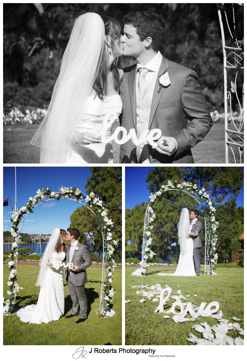 Bride and groom kissing under an flower arch with love sign - wedding photography sydney