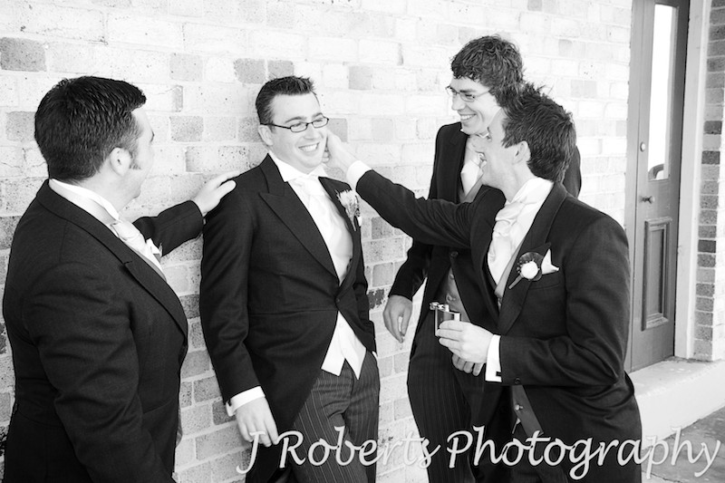 B&W groomsmen playing around prior to wedding, Georges Head Sydney - wedding photography sydney