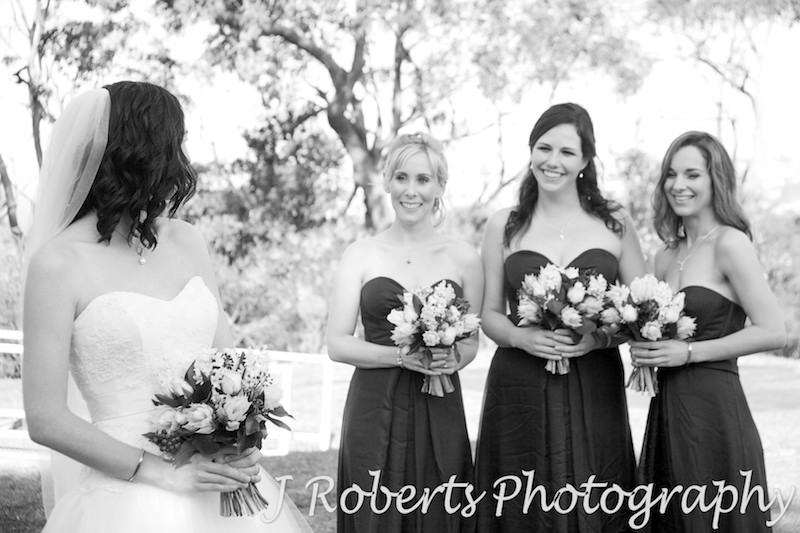 B&W bride looking at her bridesmaids - wedding photography sydney