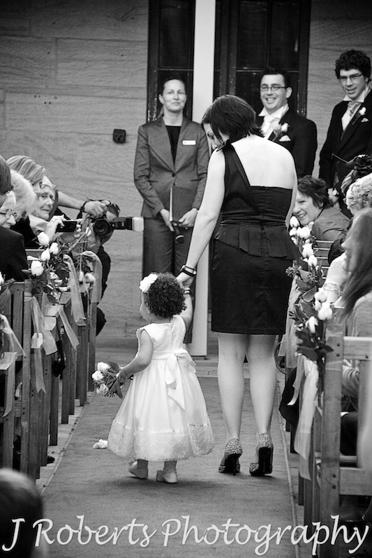 Flower girl walking down the aisle holding Mum's hand - wedding photography sydney