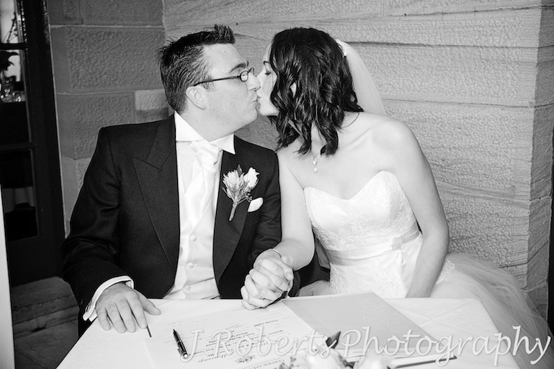 Kissing after signing the register - wedding photography sydney