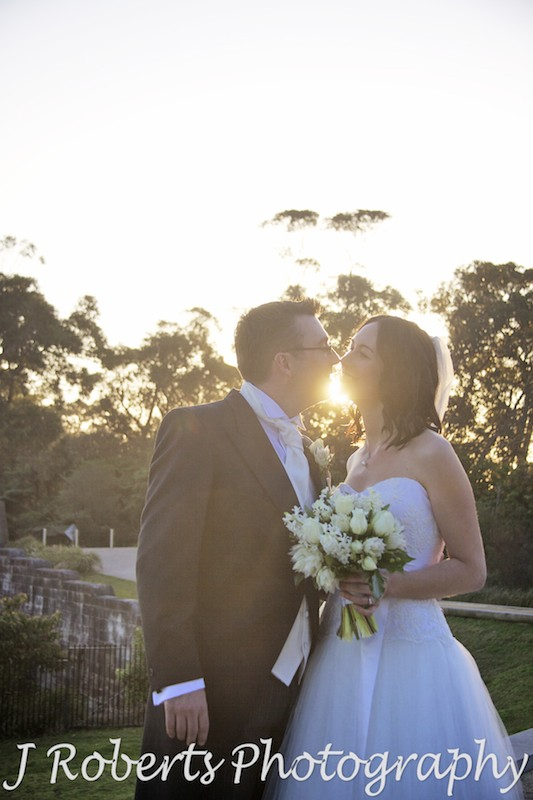 Bridal couple kissing in front of the setting sun - wedding photography sydney