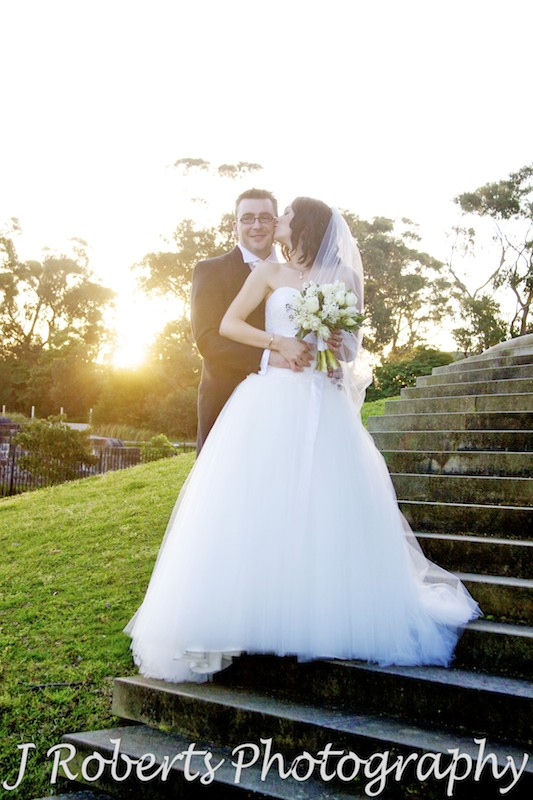 Bride kissing the groom on the cheek with setting sun behind - wedding photography sydney