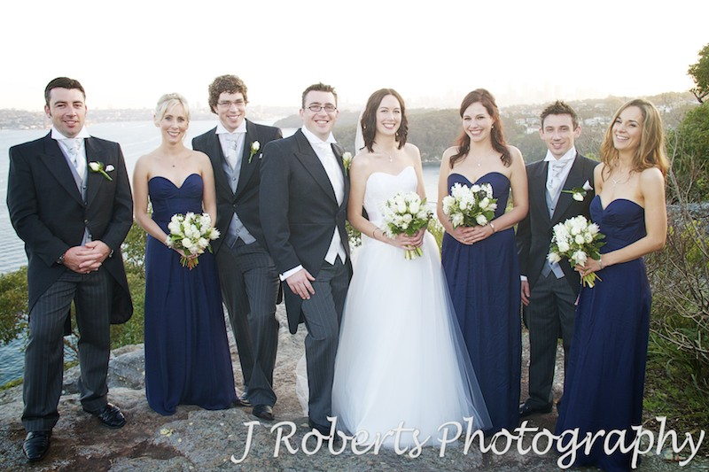 Bridal party laughing with Sydney Harbour in the background - wedding photography sydney