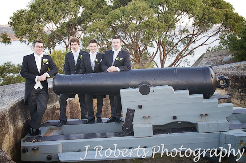 Groom and groomsmen leaning on the historic canons at Georges Headland Mosman - wedding photography sydney