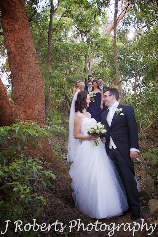 Bride and groom with bridal party in the background on the bush track near Gunners' Barracks - wedding photography sydney