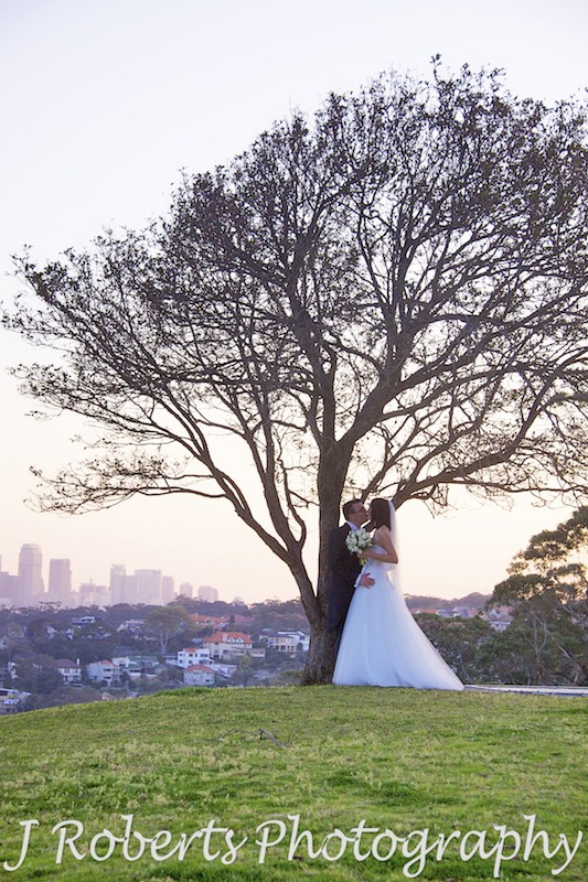 Bride and Groom kissing under tree with sunset and city skyline in the background - wedding photography sydney