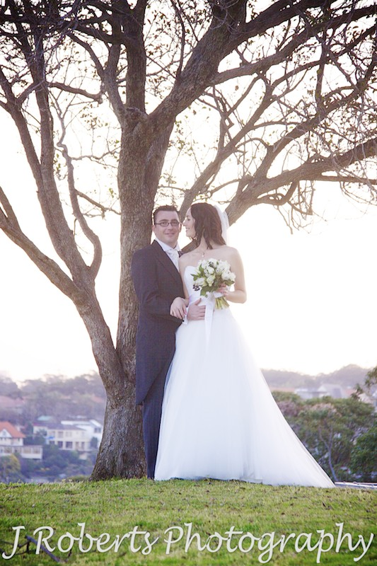 Bride looking at the groom under tree with setting sun - wedding photography sydney