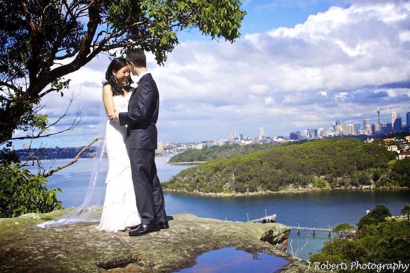 Groom kissing brides head with Sydney Harbour in the background - wedding photography sydney