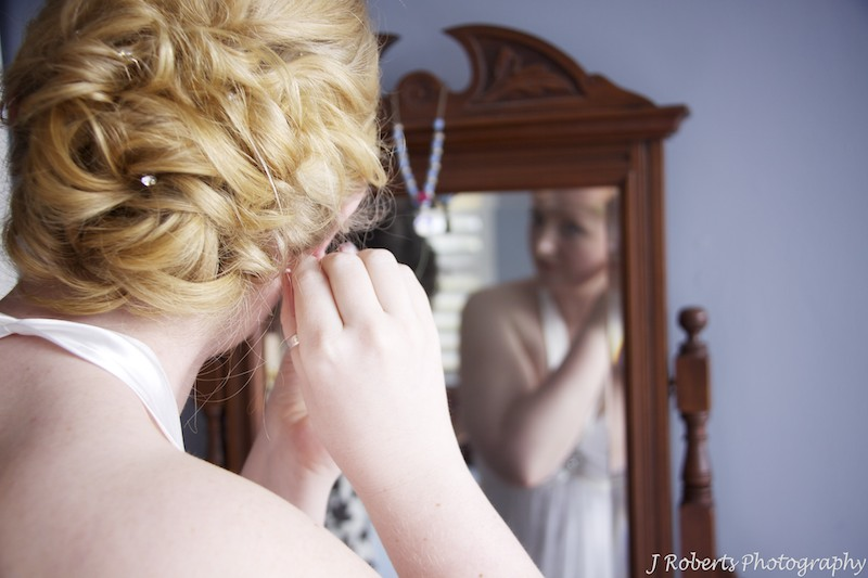 Bride putting earrings in in mirror - wedding photography sydney
