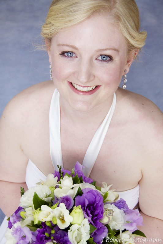 Bride looking up at camera with flowers - wedding photography sydney