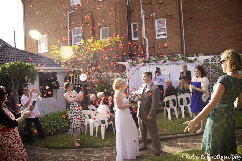 Bride and groom under rose petal cannons - wedding photography sydney