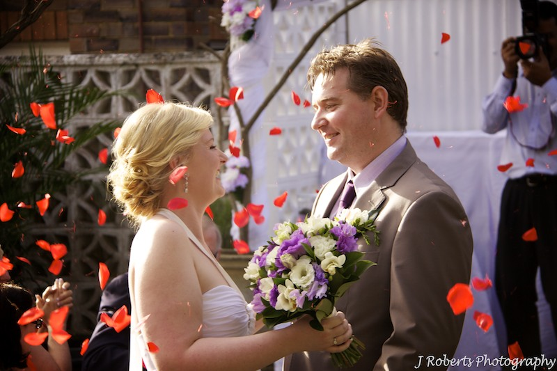 Bride and groom laughing with rose petals falling - wedding photography sydney