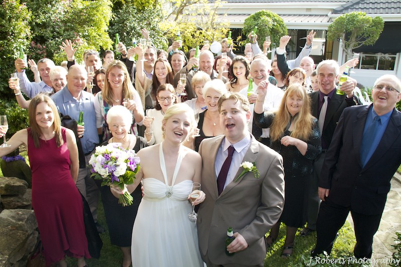Bride and groom cheering with all guests - wedding photography sydney