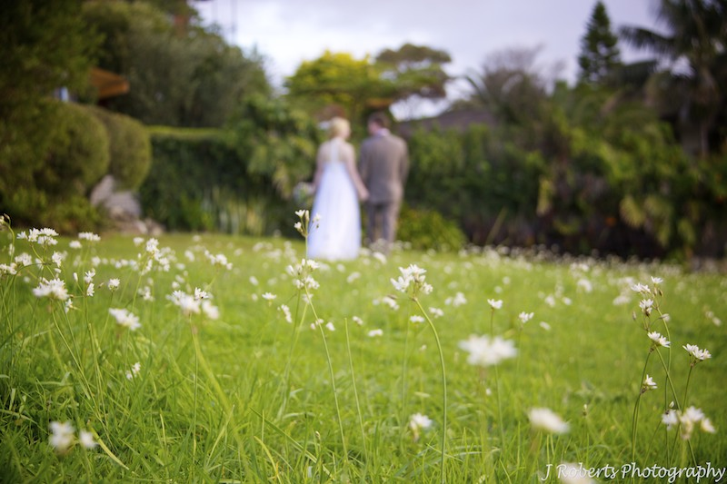 Bride and groom walking through white flowers - wedding photography sydney
